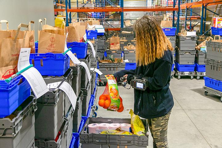 Une jeune fille qui travaille dans un supermarché drive et qui scanne des articles.